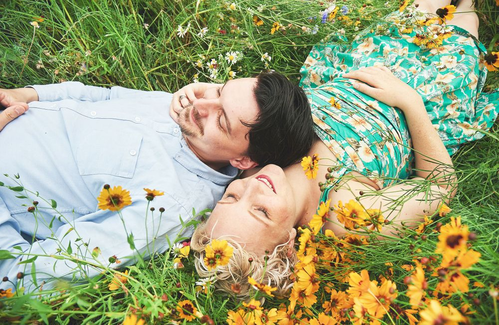 newly engaged couple lay amongst the wildflowers smiling by Norfolk wedding photographer Faye Amare