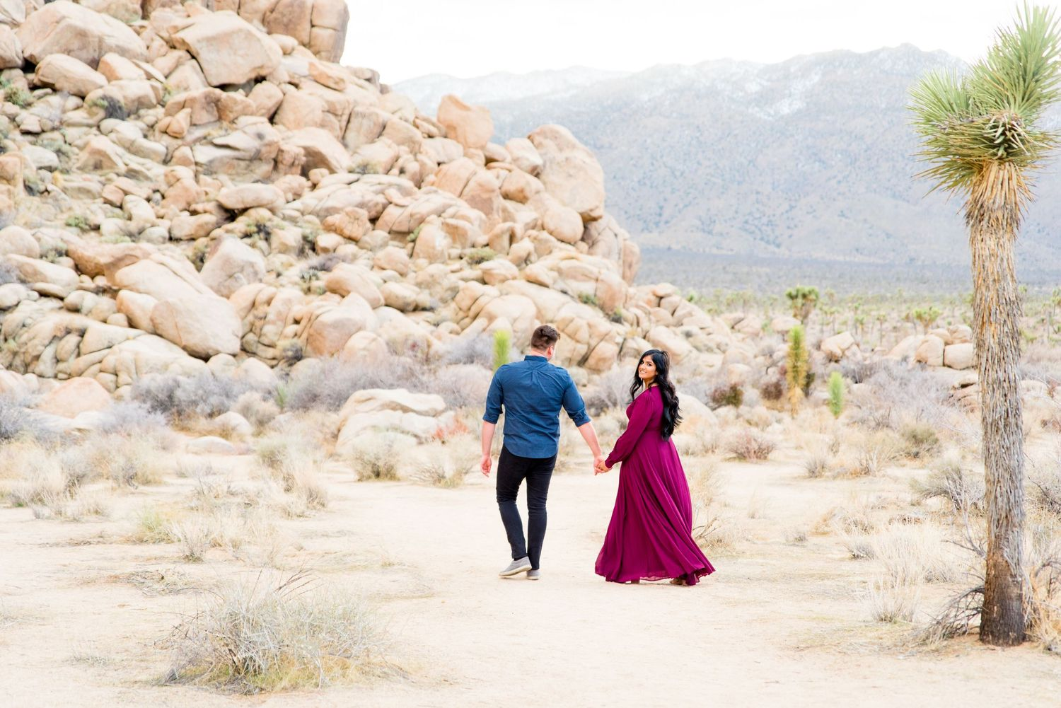 woman in dark red dress looks back as her fiance leads her through Joshua Tree National Park