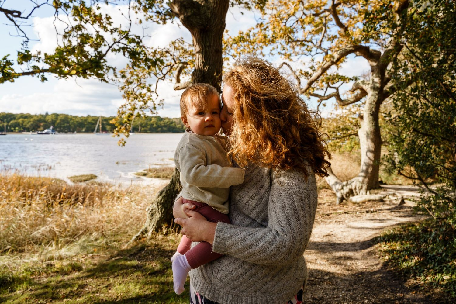 A mother kisses her baby daughter by the Beaulieu river in the New Forest on a family photoshoot.