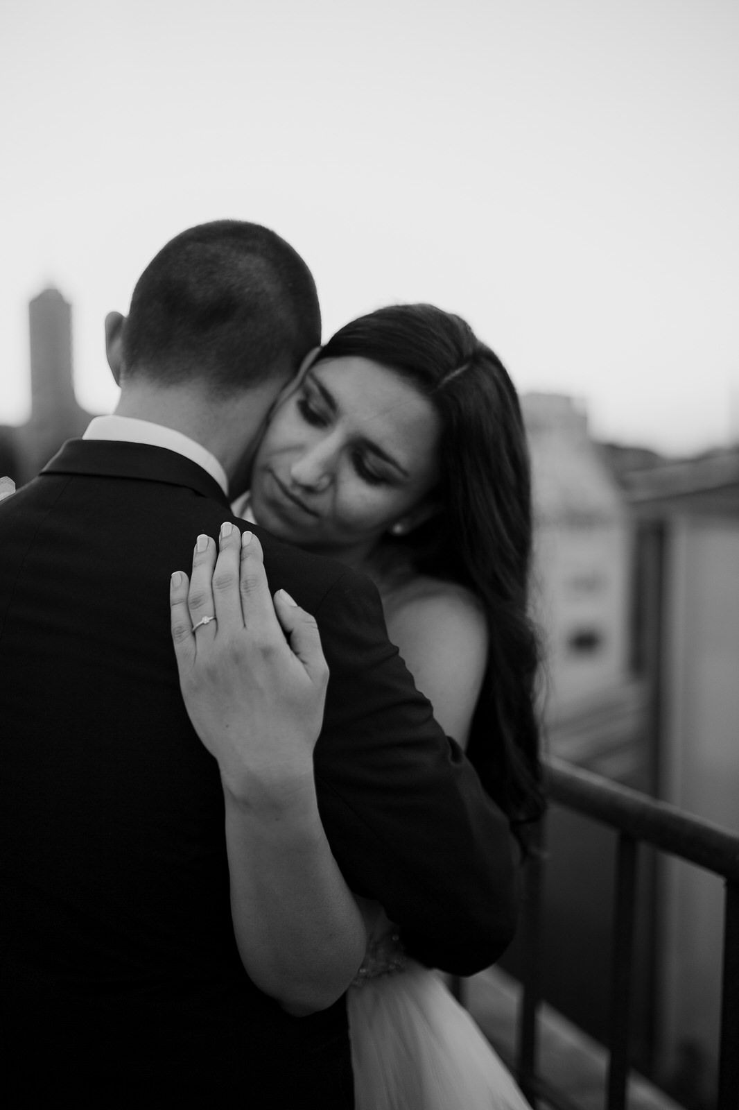 Bride and groom hugging each other on a rooftop in Paris