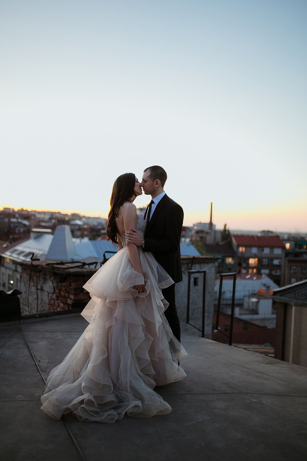 Bride and groom on a rooftop in sunset