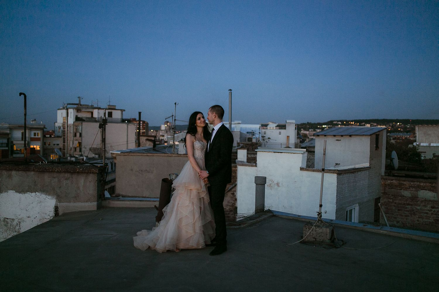 Bride and groom on a rooftop at sunset