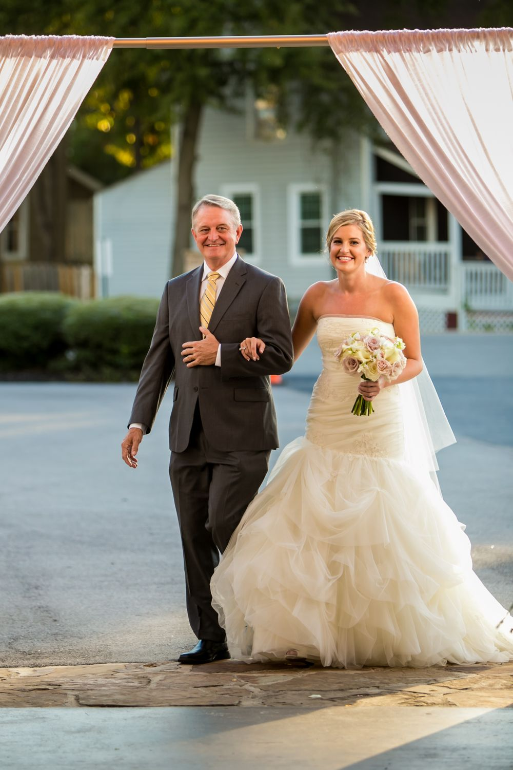 Bride Ashley is walked down the aisle by her father during her wedding at Stone River in West Columbia, SC