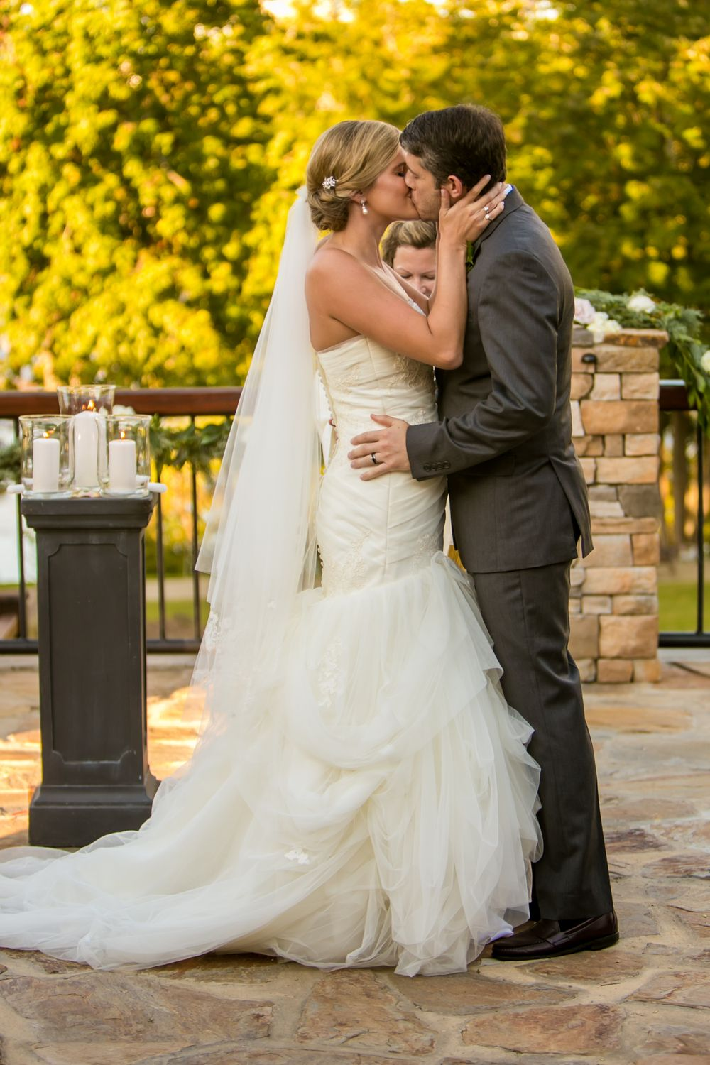 Bride Ashley and groom Jared have their first kiss during their wedding ceremony at Stone River in West Columbia, SC