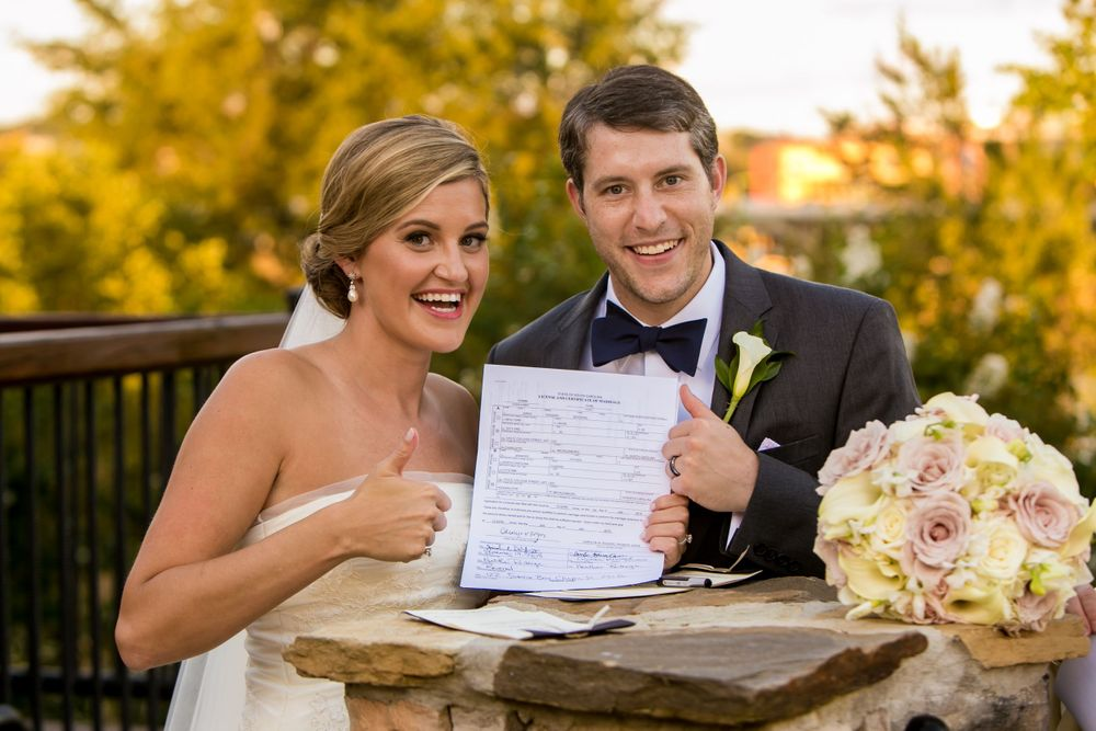 Bride Ashley and groom Jared show their marriage license after their wedding at Stone River in West Columbia, SC