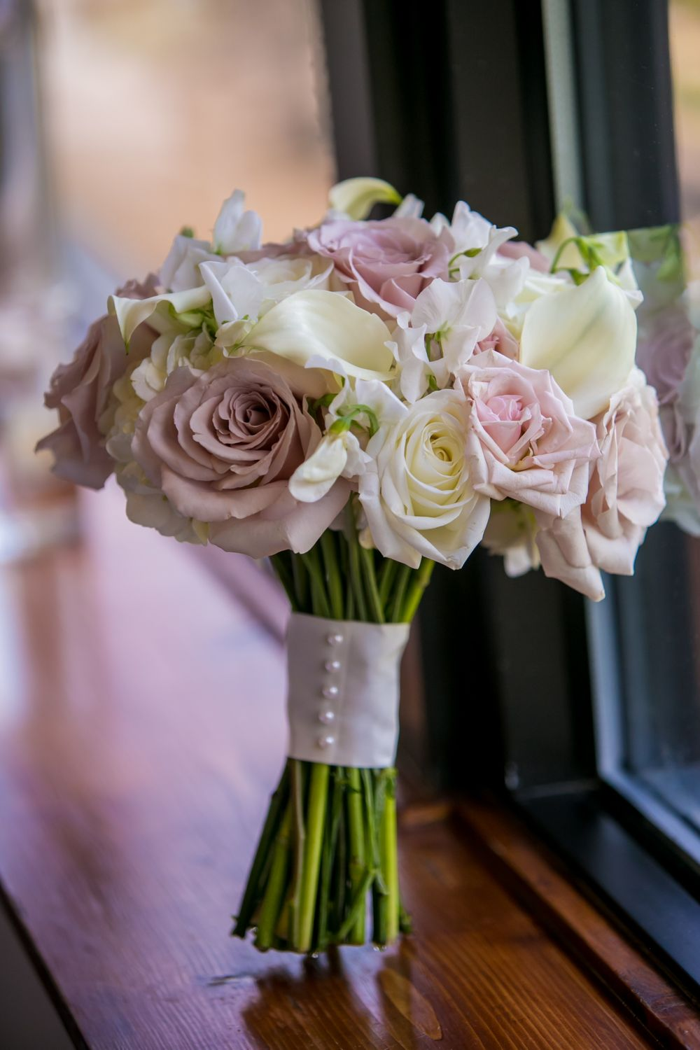Ashley's bridal bouquet in a window before a wedding at at Stone River in West Columbia, SC