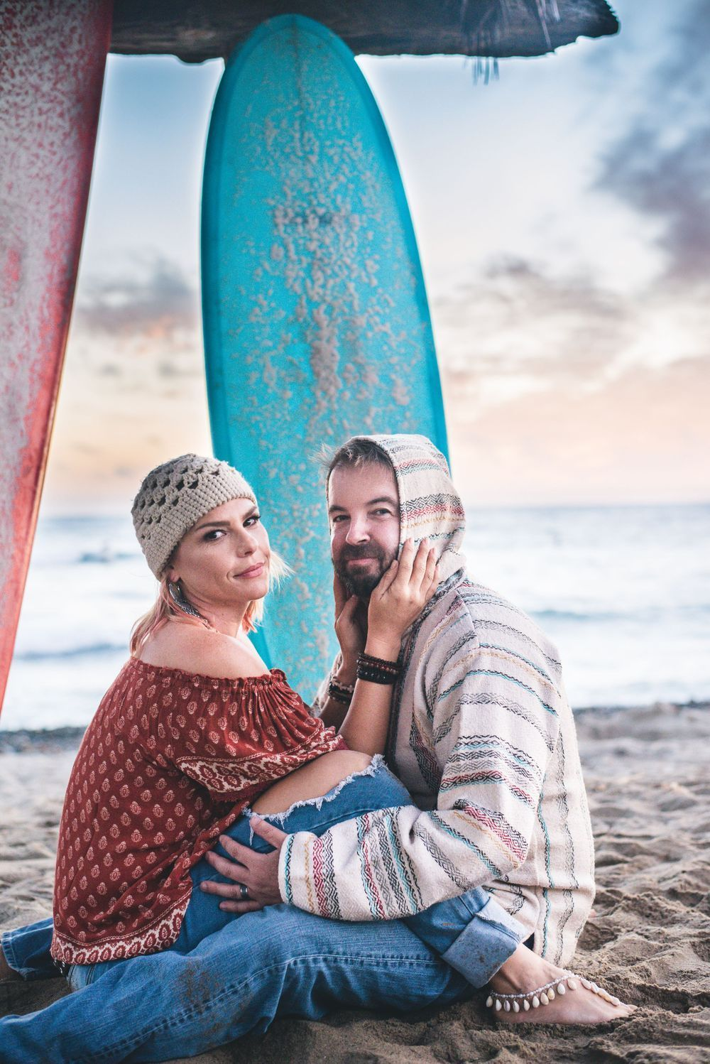 Photo of a husband and wife on the beach with surfboards in San Clemente, CA