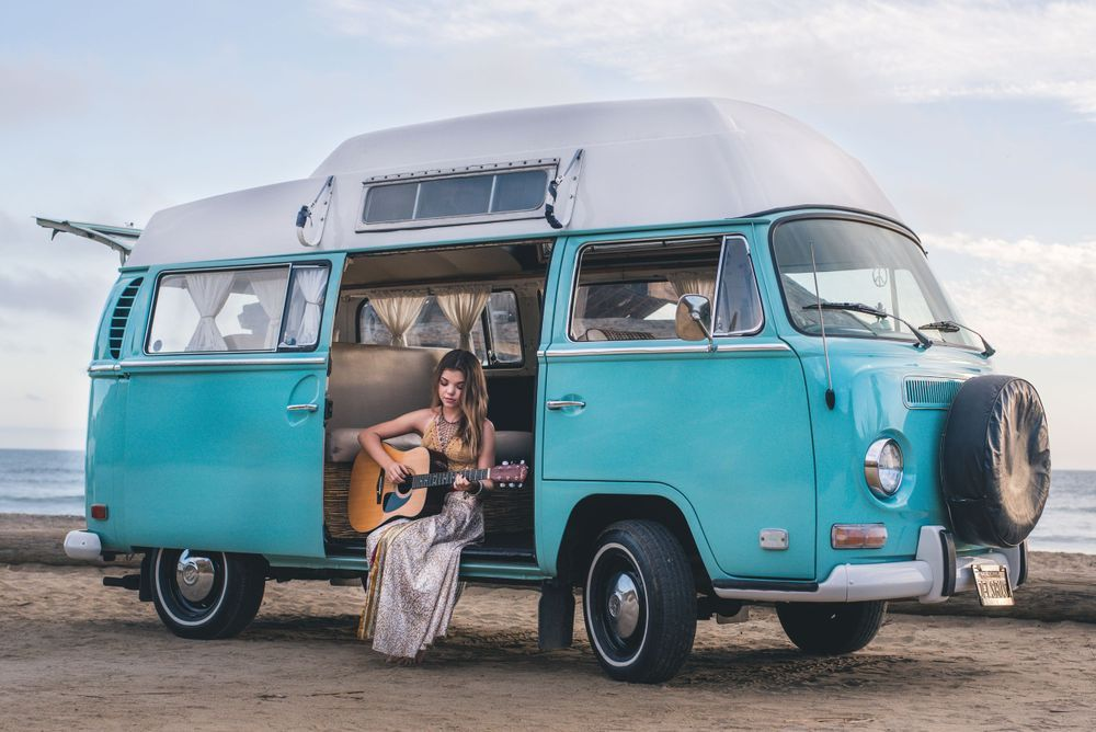Photo of a girl playing a guitar in a VW Bus in San Clemente, CA
