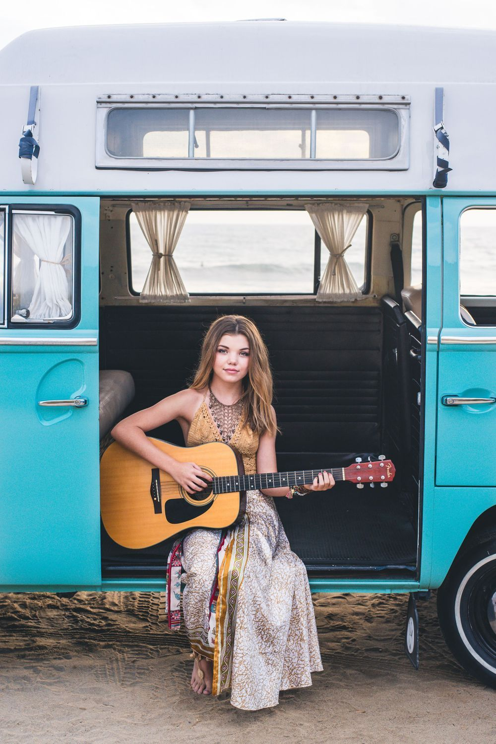Photo of a teen girl playing a guitar in a VW Bus in San Clemente, CA