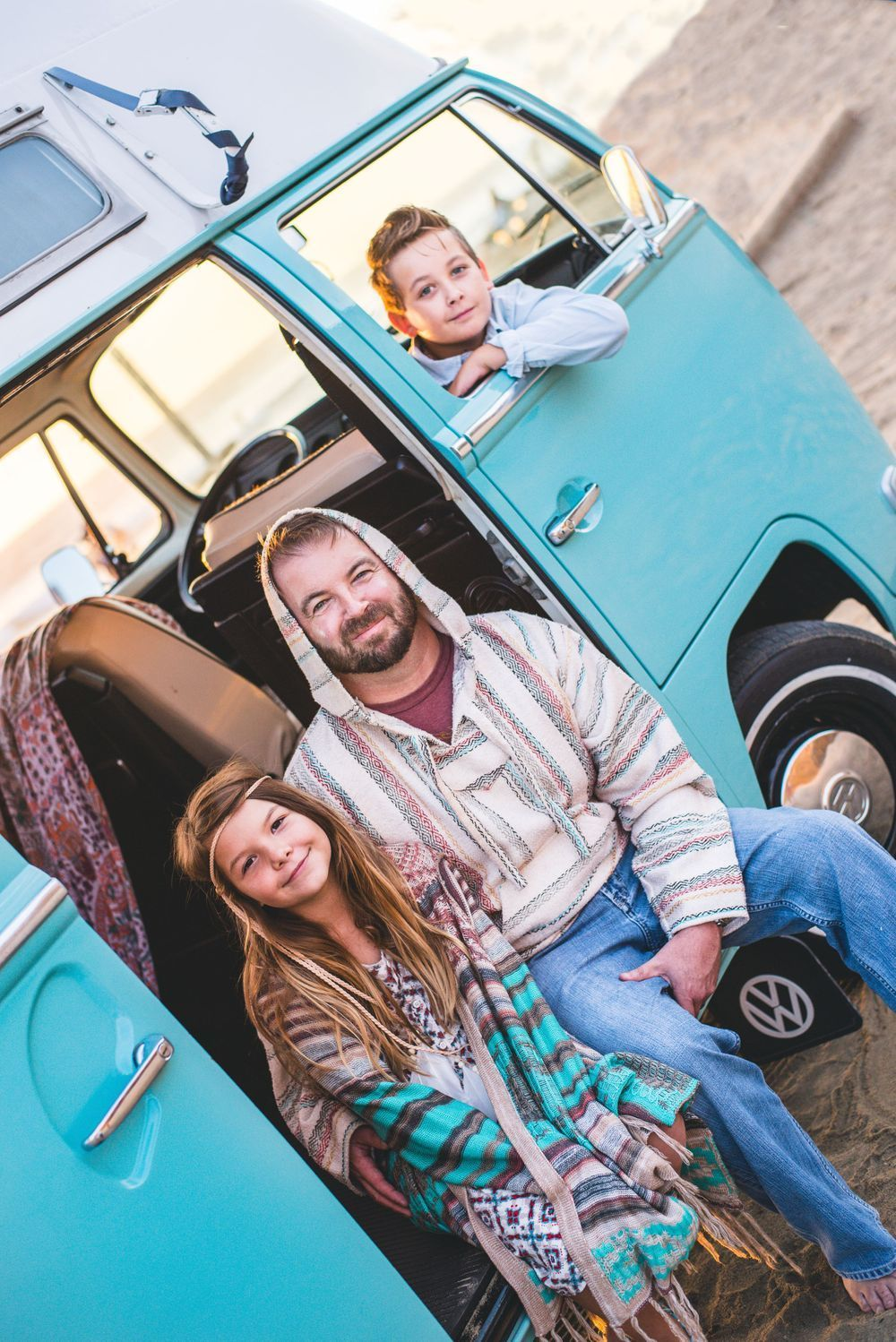 Photo of a family sitting in a VW Bus on the beach in San Clemente, CA