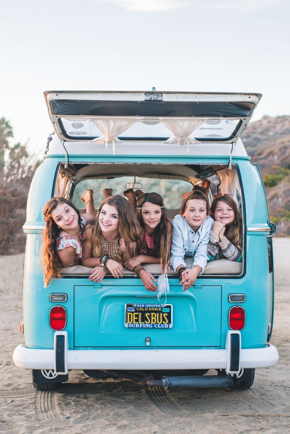 Photo of siblings in the back of a VW Bus on the beach in San Clemente, CA