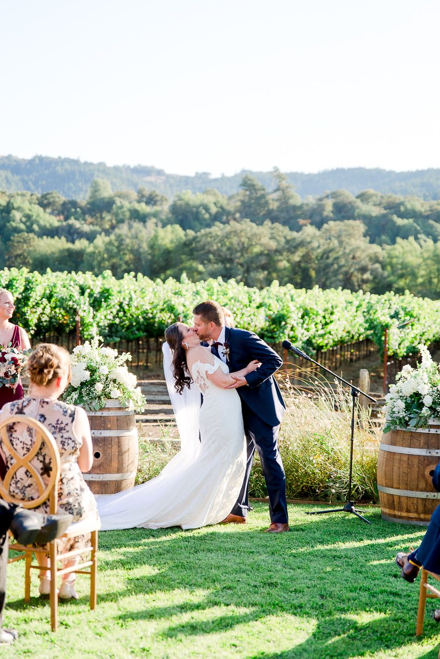 bride and groom's first kiss in front of mountains at outdoor Pennyroyal Farm wedding