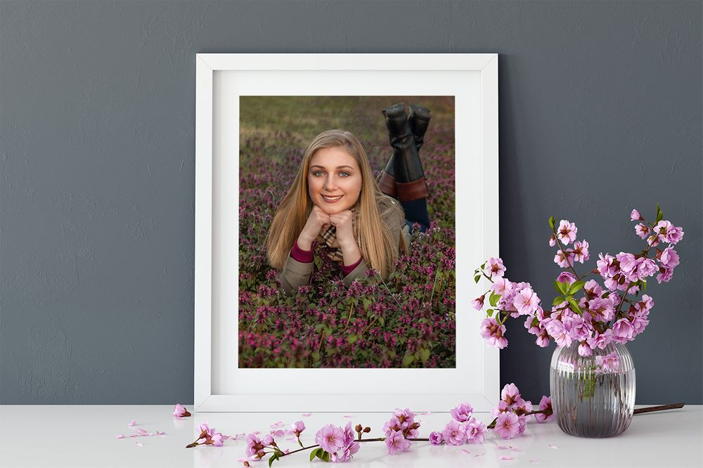 framed photo of a high school senior posing in a flower patch