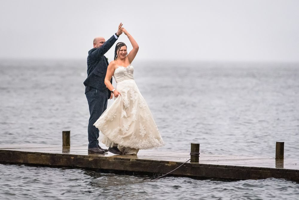 Bride and groom dancing on jetty beside Windermere during storm Dennis