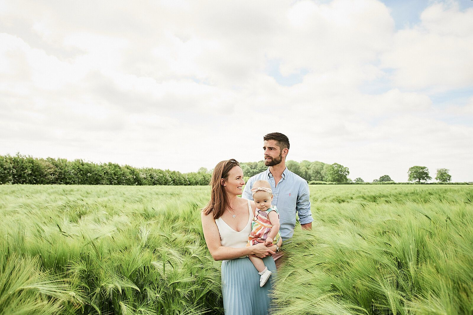mother, father and young daughter walk through a field of wheat by Faye Amare Photography