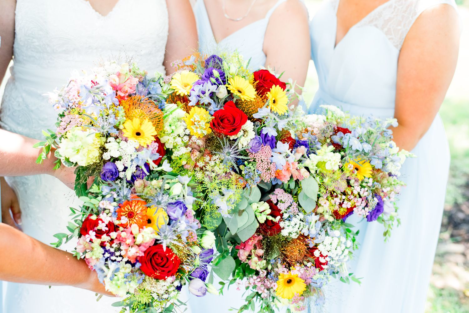 bridesmaids in blue dresses holding rainbow wedding bouquets