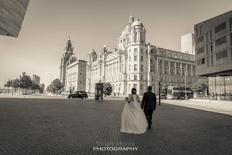 bride and groom walk along liverpools iconic waterfront liver building in the distance