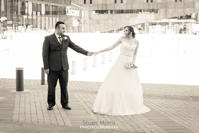 bride and groom holding hands arms outstretched on the liverpool waterfront