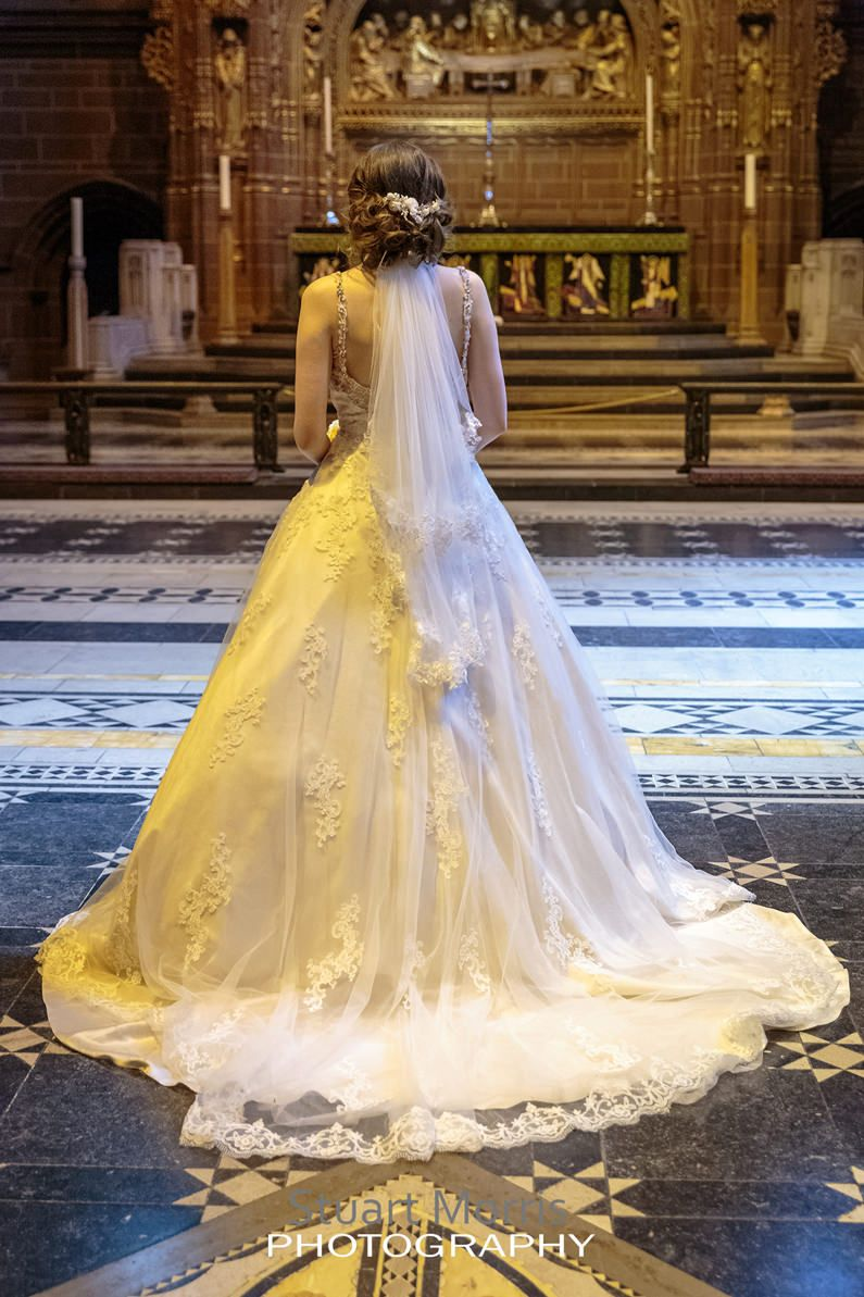 the bride in her stunning wedding dress stands at the altar in liverpool cathedral