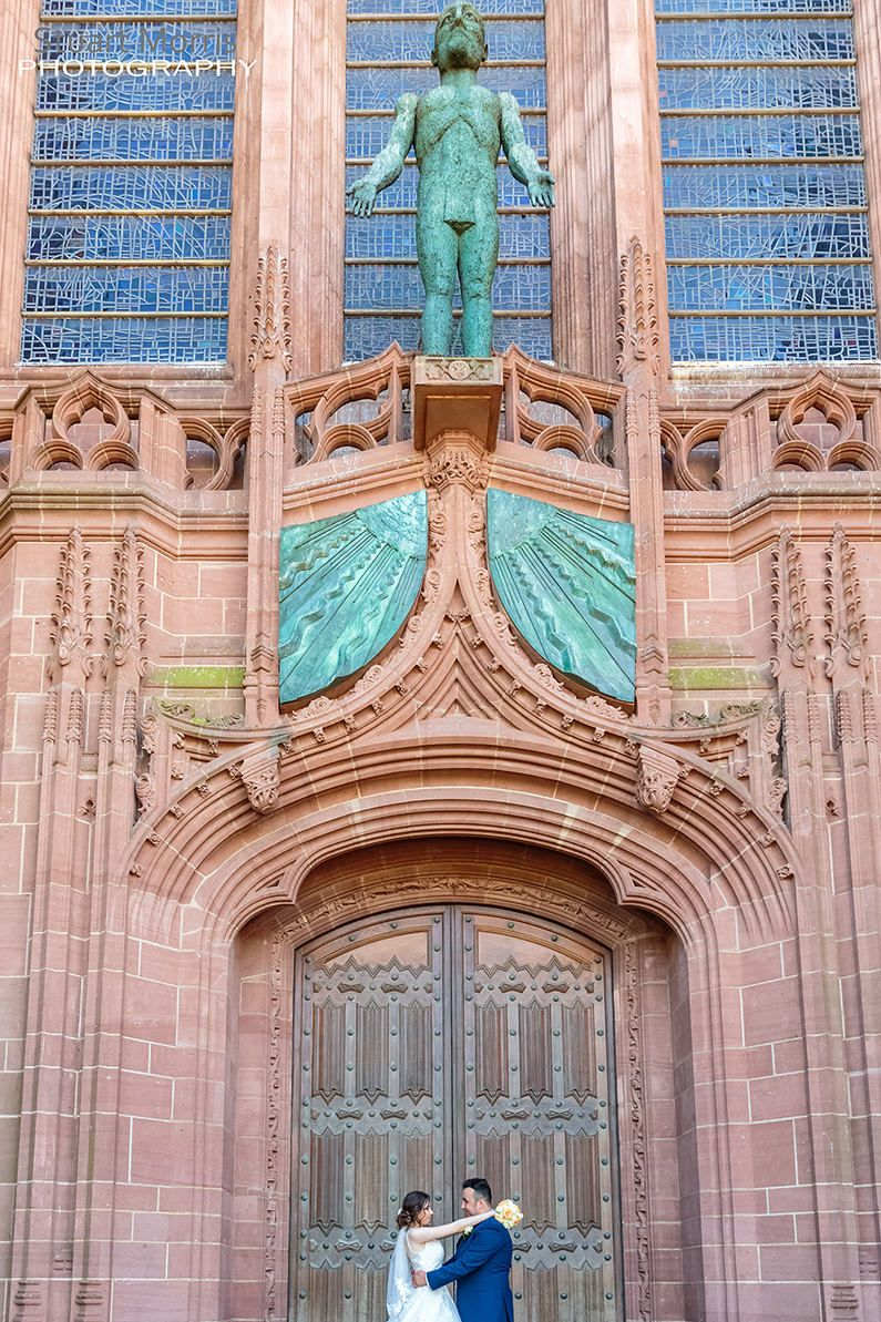 bride and groom with their arms around each other stand in the ornate doorway at liverpool cathedral
