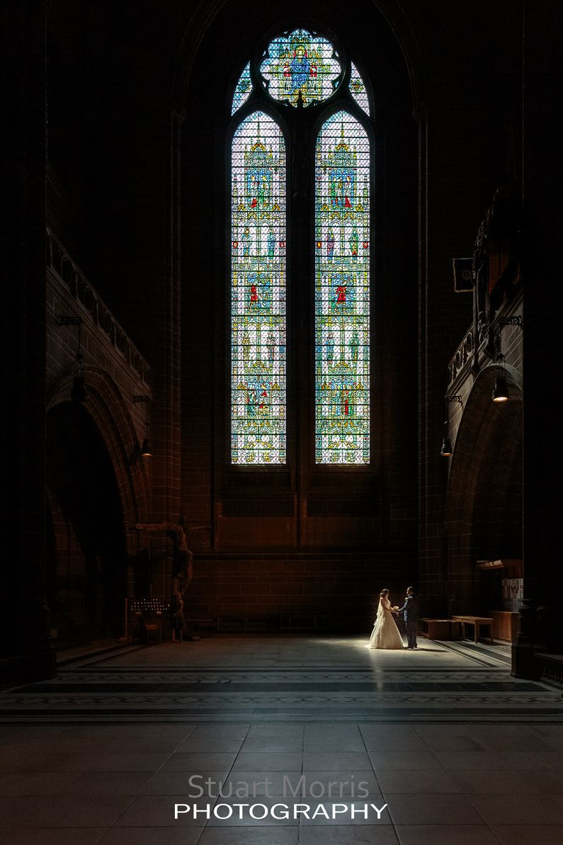 bride and groom stand holding hands stand in a ray of sunlight coming through a huge stained glass window