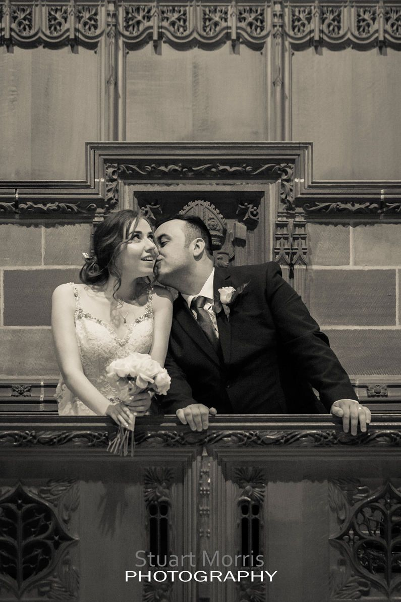 groom kisses his bride on the cheek behind a pew at Liverpool cathedral