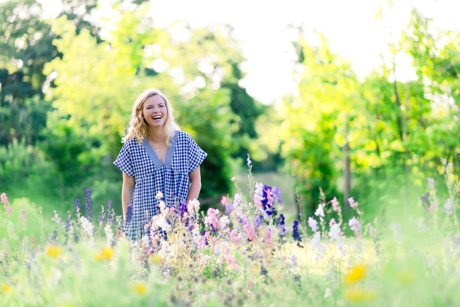 young woman laughing in field of flowers at The Marmalade Lily in Cincinnati OH for summer senior pictures