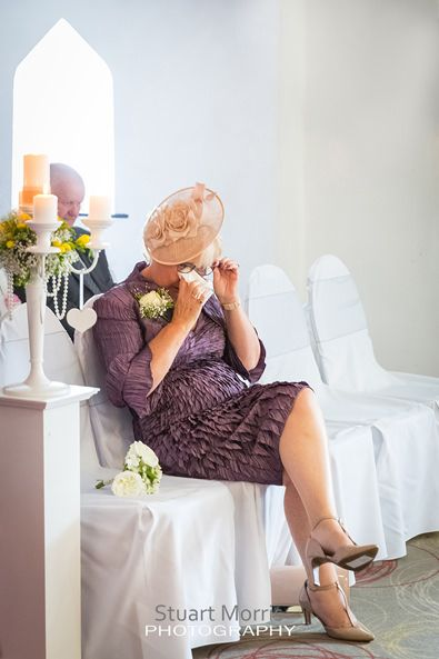 mother of the bride sits crying as she wipes a tear away from her eye with a tissue