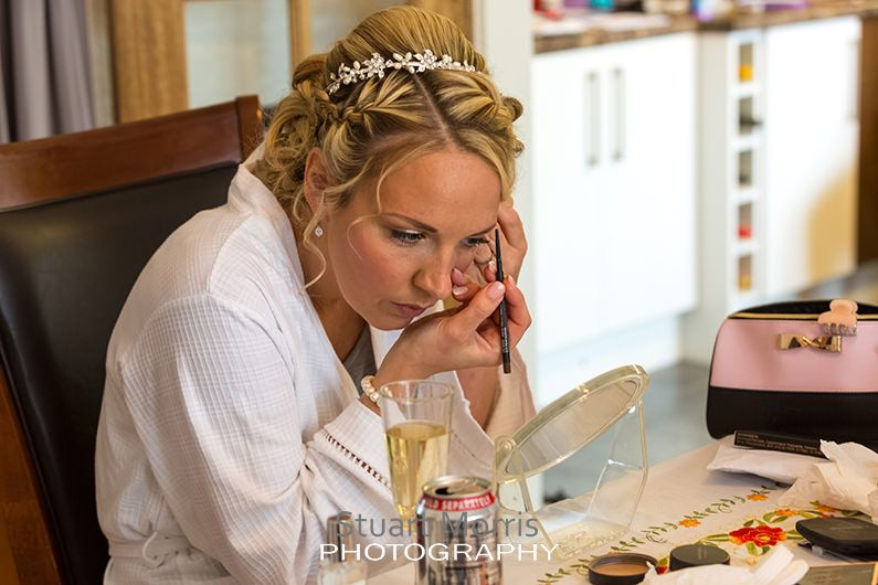 bride leans over the table as she does her eye makeup in the mirror