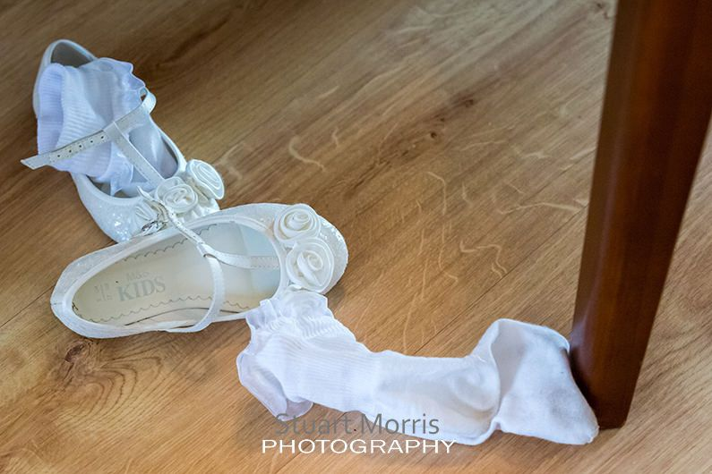 flower girls shoes and socks lying on the wooden kitchen floor