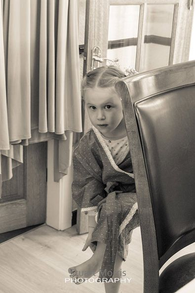 young flower girl in her dressing gown leans on the back of a chair and rubs her foot