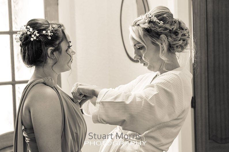 bride adjust the bridesmaids dress in her parents hallway during the bridal prep