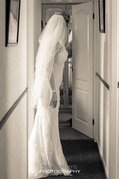 bride stands looking down the hallway in her parents house during the bridal prep
