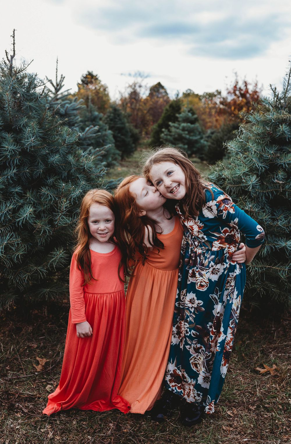 sisters hugging at a tree farm mini session