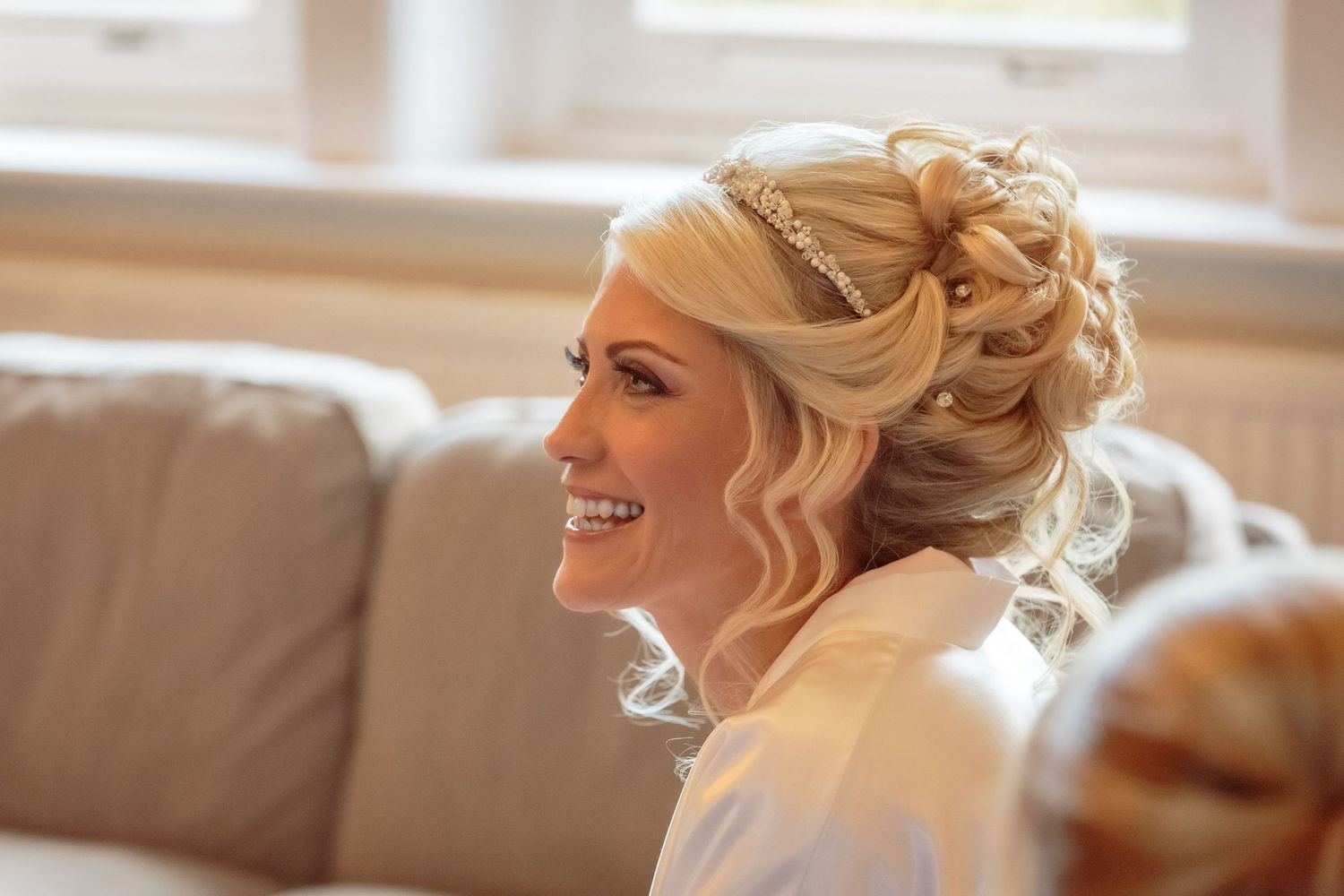 bride sits on the couch smiling during the bridal prep