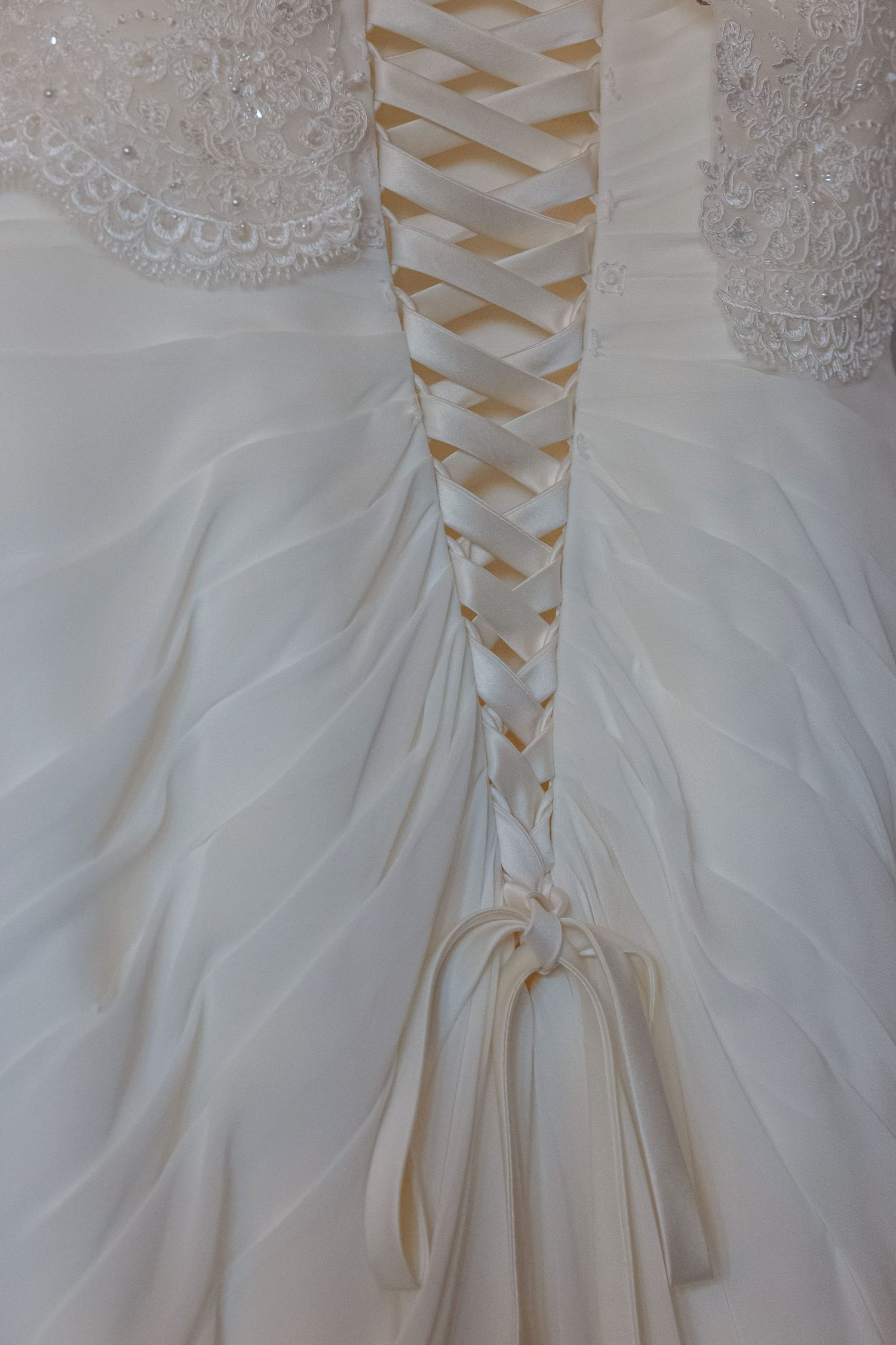 detail shot of the lacing on the back of the brides dress