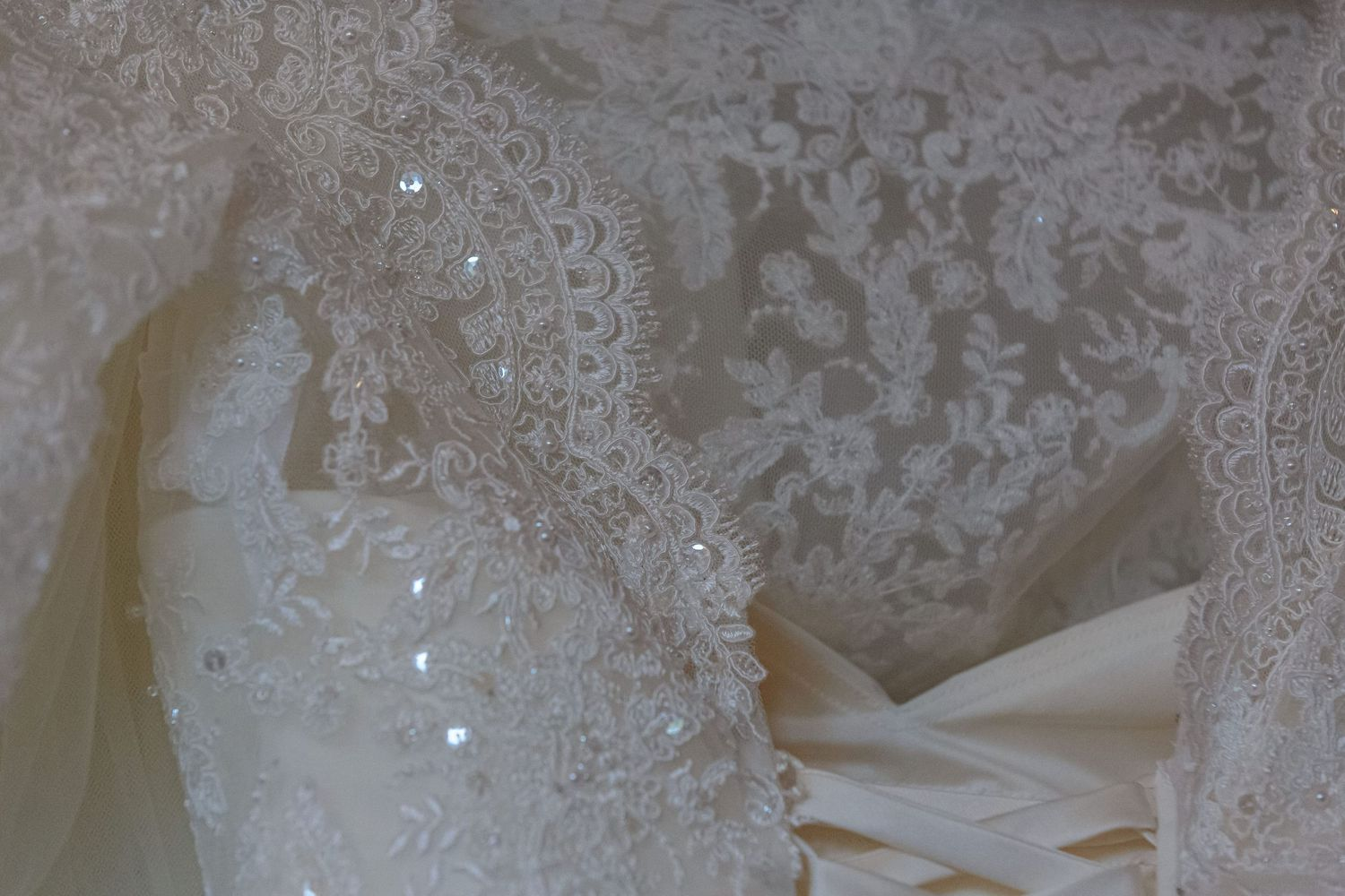 detail shot of the lace on the brides dress and bolero