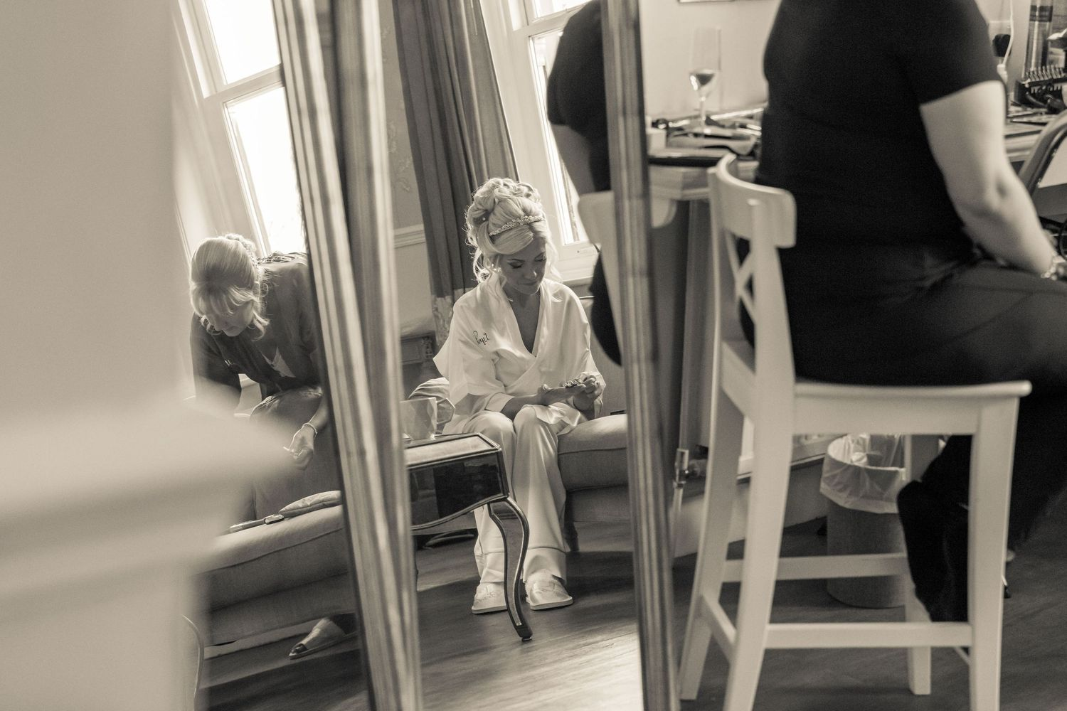reflection shot in an ornate mirror of the bride sitting in her pyjamas during the bridal suite