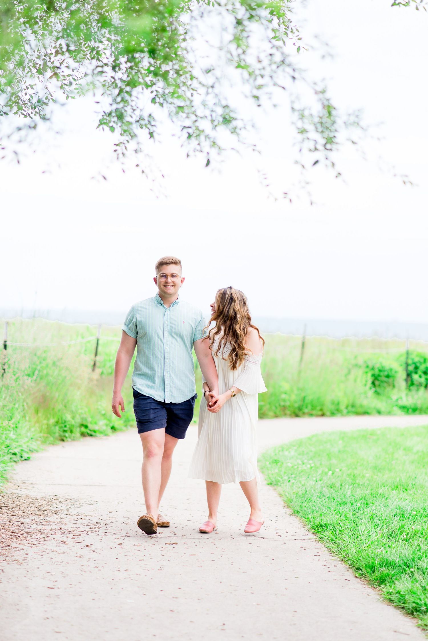 young engaged couple laughing and walking on a gravel path at Montrose Harbor in Chicago in the summer