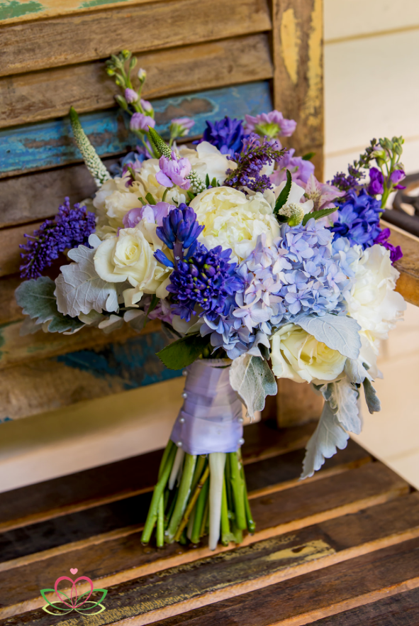 A floral bouquet on a weathered bench before a wedding at the River Road and Jasmine House in Lexington, SC