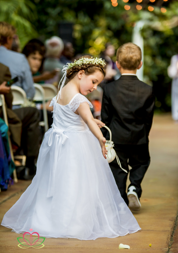 Flower girl drops flowers on aisle during a wedding ceremony at the River Road and Jasmine House in Lexington, SC
