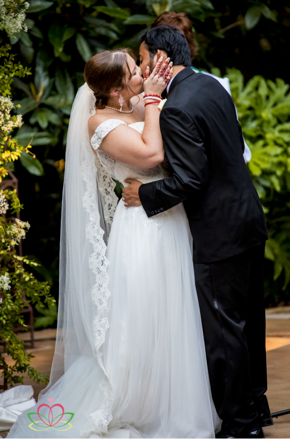 Bride and groom share their first kiss during a wedding ceremony at the River Road and Jasmine House in Lexington, SC
