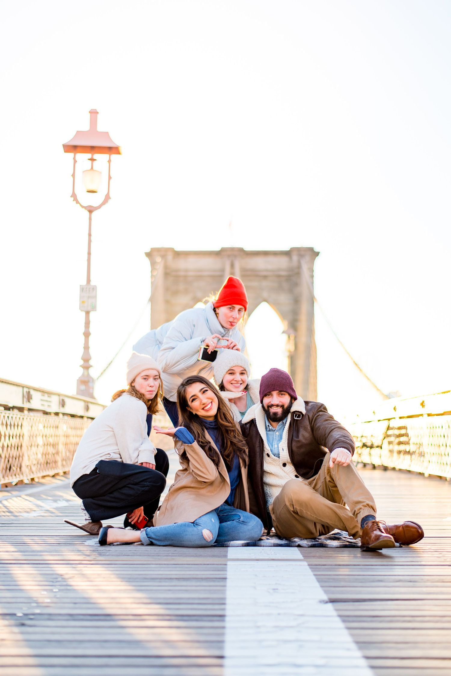 three strangers in NYC smile with an engaged couple in the middle of Brooklyn Bridge at sunrise