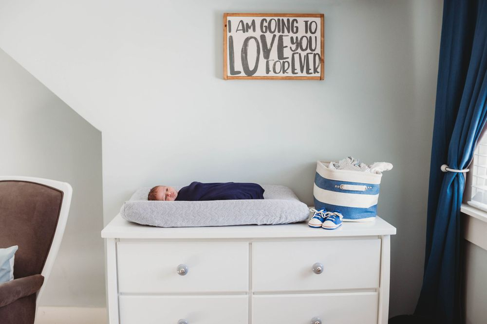 newborn on changing table by leominster newborn photographer
