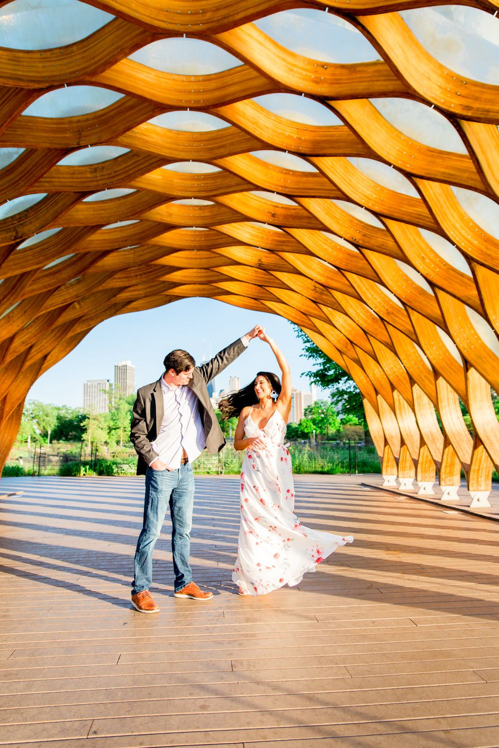 man in suit twirling woman under Honeycomb at Lincoln Park for engagement pictures in Chicago at sunset