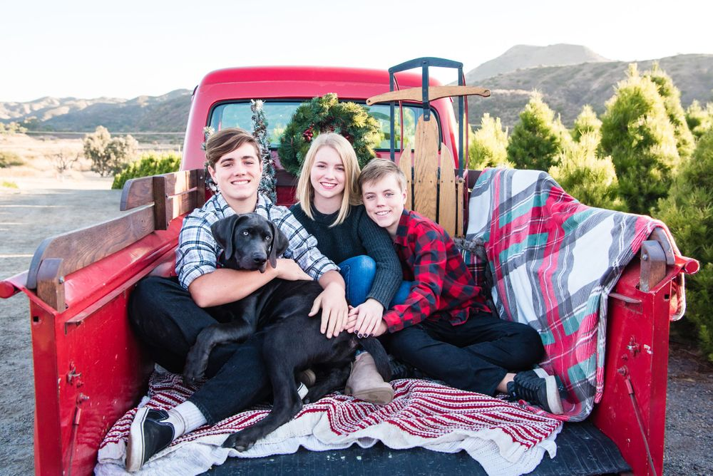 A photo of a family in the back of a vintage red pickup truck at a Christmas Tree Farm in Orange County, CA