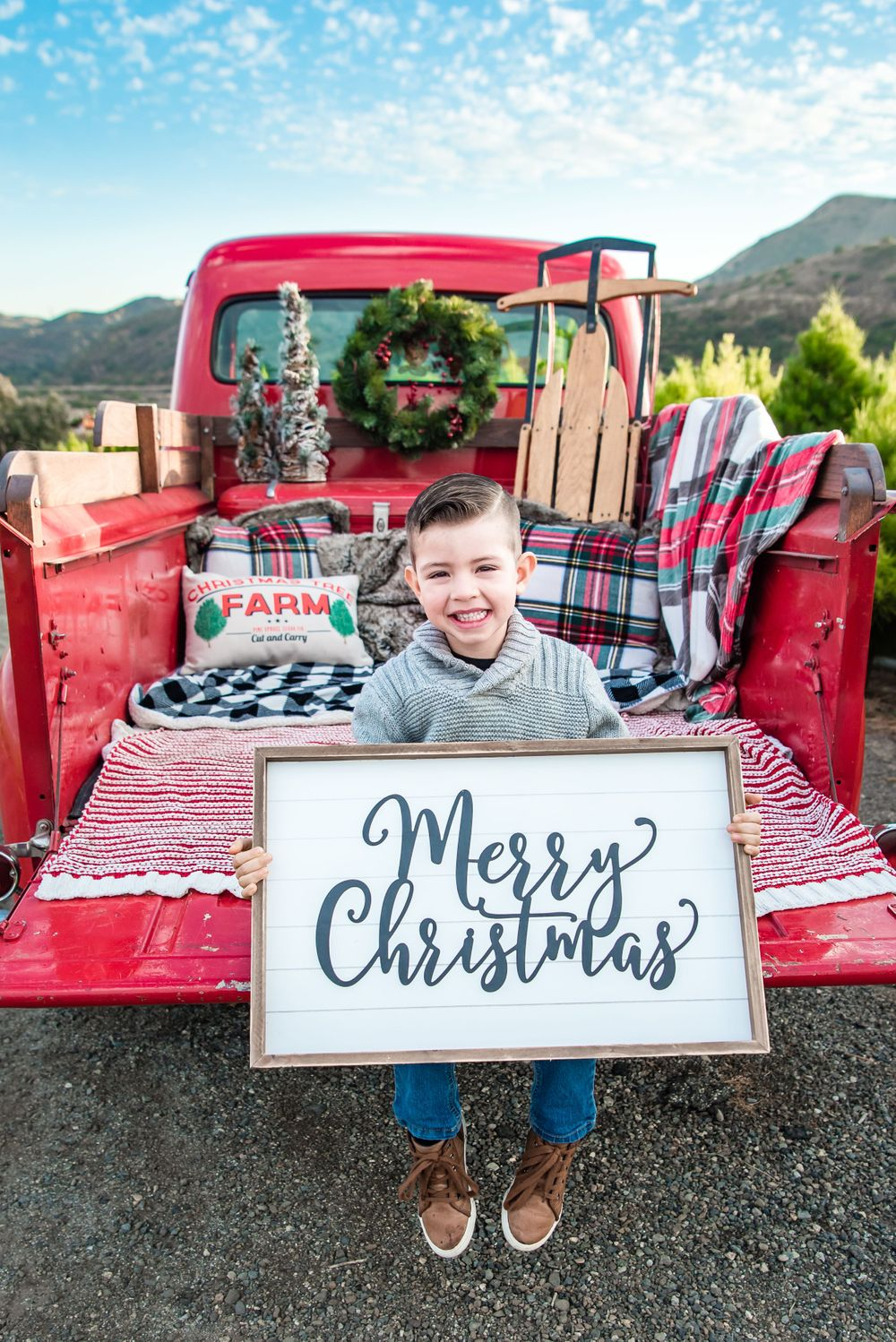 A young boy in the back of a red vintage pickup truck at a Christmas Tree Farm in Orange County, CA