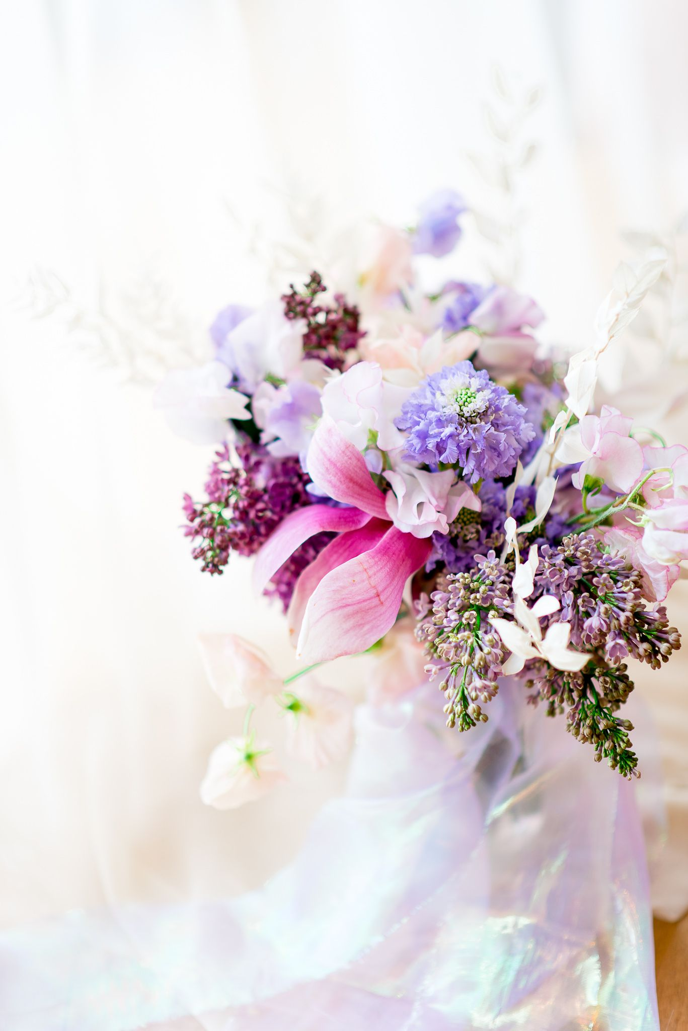 pink, purple, and white wedding bouquet with magnolias, sweet peas, and lilacs