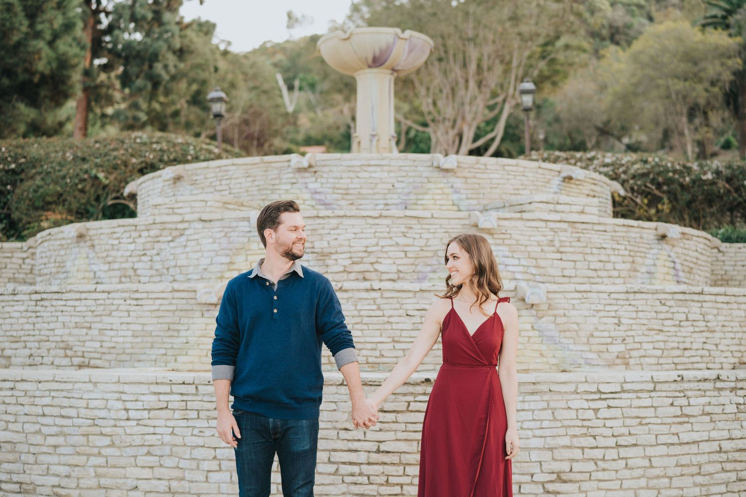 couple holding hands in front of stone fountain