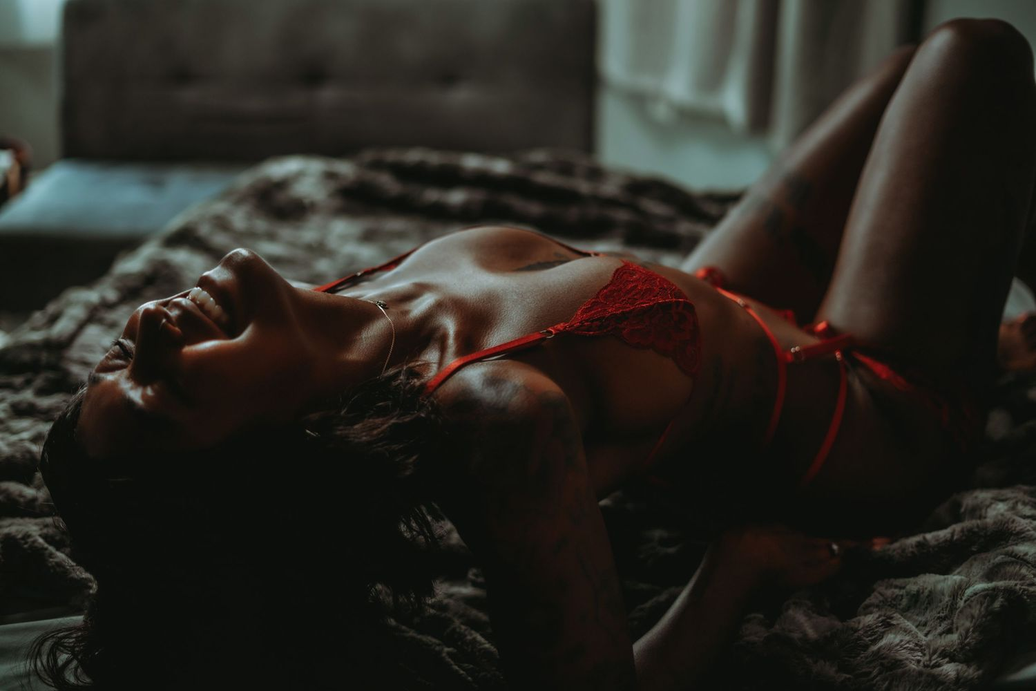 dark skinned woman arching her back on a bed and grinning, wearing red lingerie set